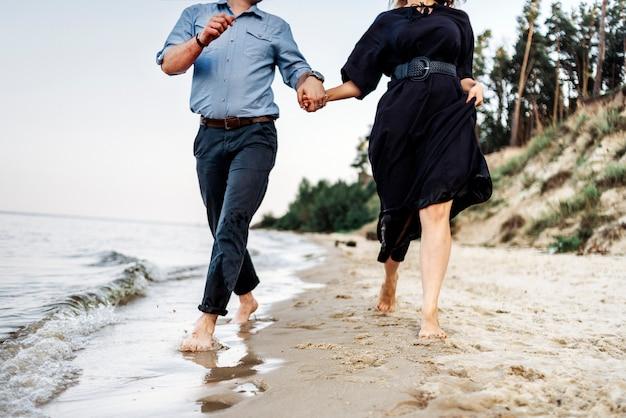 Пара бежит возле реки море океан вода держится за руки