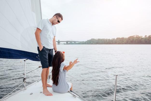 Пара плывет на яхте. молодая женщина сидит на луке и указывает сзади. она смотрит на своего парня. он улыбается и смотрит на нее. парень трогает брюнетку. он доволен.