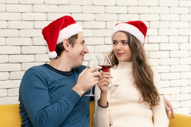 Couple is sitting drinking red wine on the sofa.