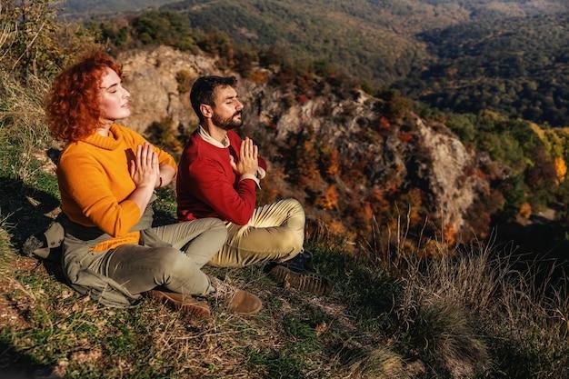 カップルは蓮華座に座って、太陽に向かって瞑想しています