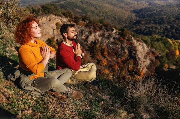 Couple is sitting in lotus position and meditating towards the sun
