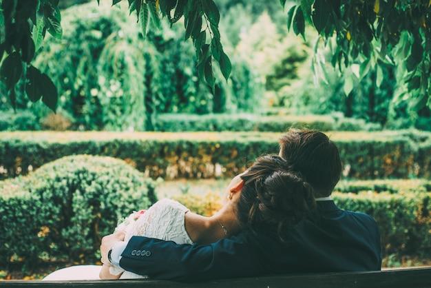 Пара сидит на скамейке в парке