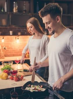 함께 부엌에서 요리하는 동안 몇 웃고있다.