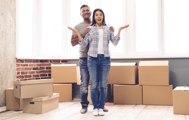 Couple is smiling while standing near the packed boxes