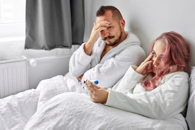 カップルは深刻な結果を心配しています、彼らはテストを使用して妊娠について設立され、ベッドに不幸に悲しんで座っています
