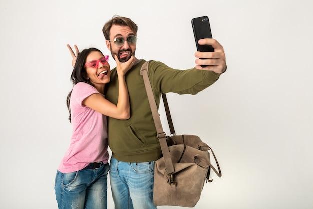 Coppia isolata, bella donna sorridente in maglietta rosa e uomo in felpa con borsa da viaggio, indossa jeans e occhiali da sole, divertirsi, viaggiare insieme facendo foto divertenti selfie sul telefono