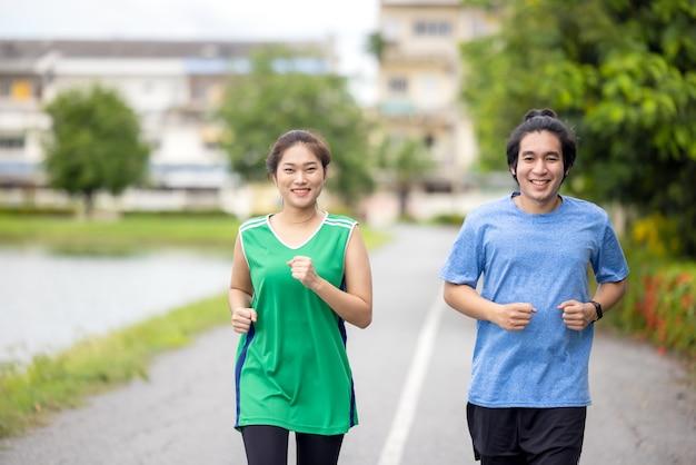 Пара бегает трусцой и бегает в естественной среде летним утром