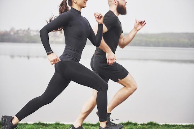 Пара бегом и работает на открытом воздухе в парке возле воды. молодой бородатый мужчина и женщина, осуществляющих вместе утром
