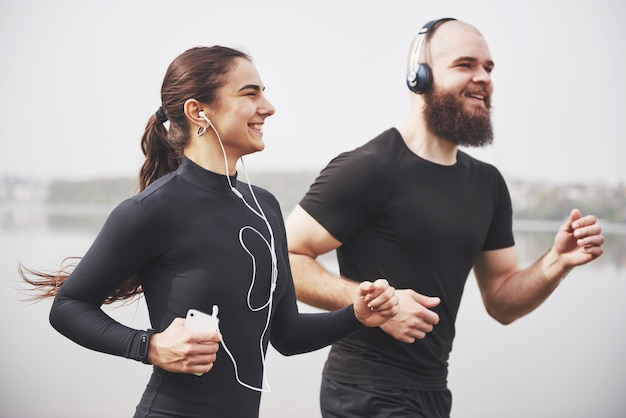 ジョギングや屋外の水の近くの公園で走っているカップル。若いあごひげを生やした男性と女性が朝一緒に運動