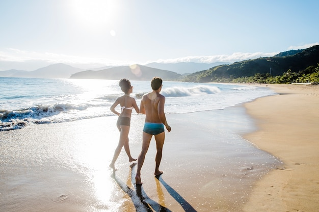 ビーチでジョギングするカップル