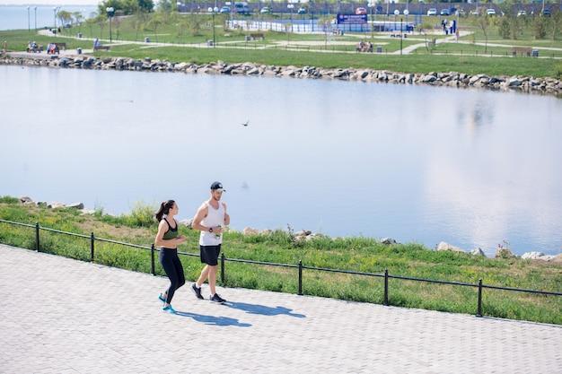 都市公園のバックグラウンドでジョギングカップル