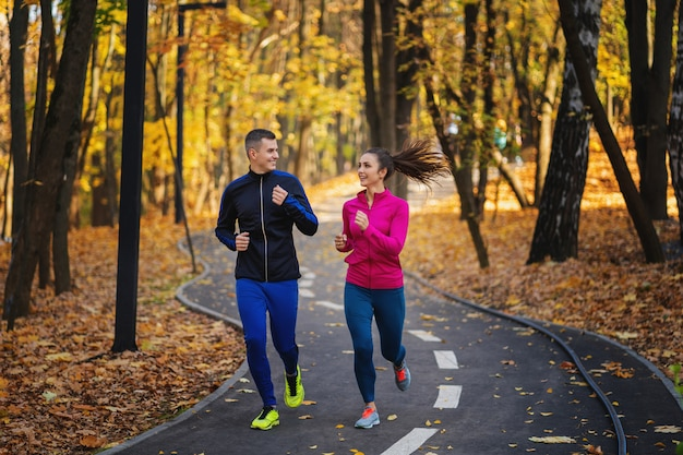 Couple jogging and running outdoors in autumn nature