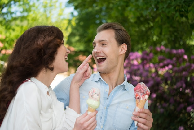Пара шутит и веселится во время еды мороженого