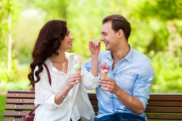 Couple joking and having fun while eating an ice cream