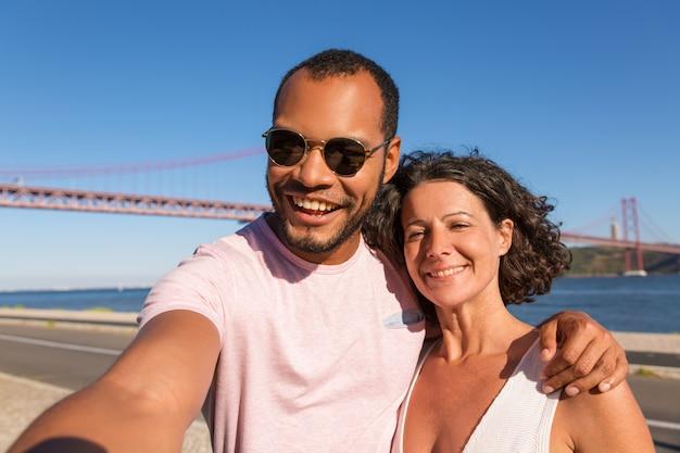 Couple of joyful tourists taking selfie on city promenade
