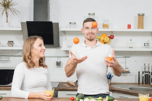 Couple juggling with fruits