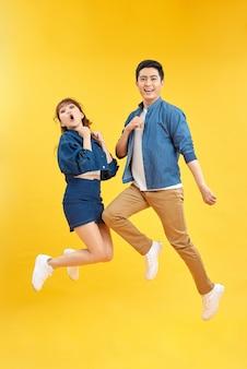 Пара прыгает высоко поднятыми кулаками орать крик крик громко носить повседневные джинсы джинсовые белые футболки изолированный желтый фон