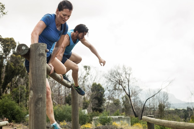 Couple jumping over the hurdles during obstacle course