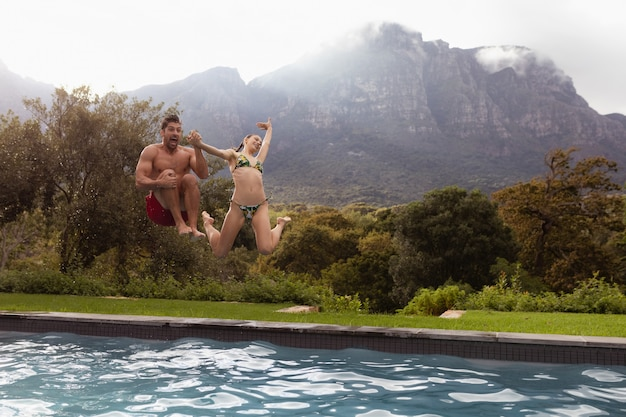Couple jumping together in the swimming pool at backyard