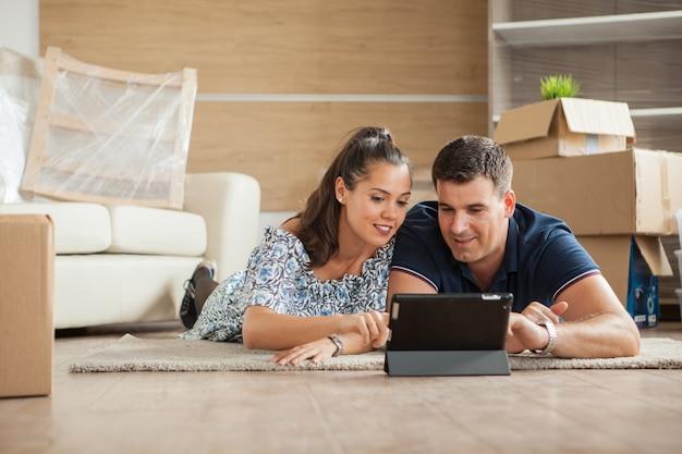 新しい家に引っ越したばかりのカップルがタブレットpcで家具をオンラインで買い物しています