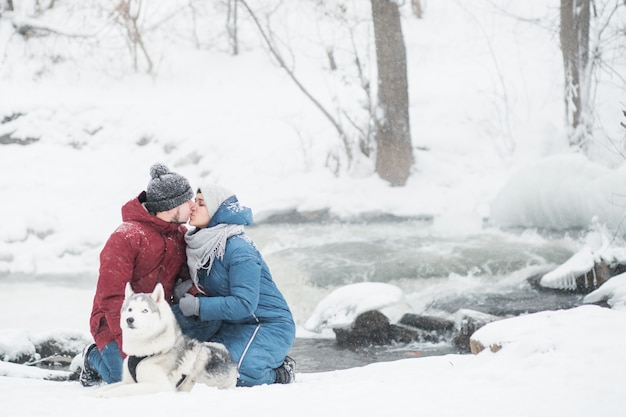 Couple kiss sitting with siberian husky in winter. waterfall. valentine day. snowfall. happy family. dog. high quality photo