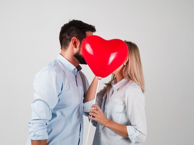 Couple kissing behind balloon for valentines
