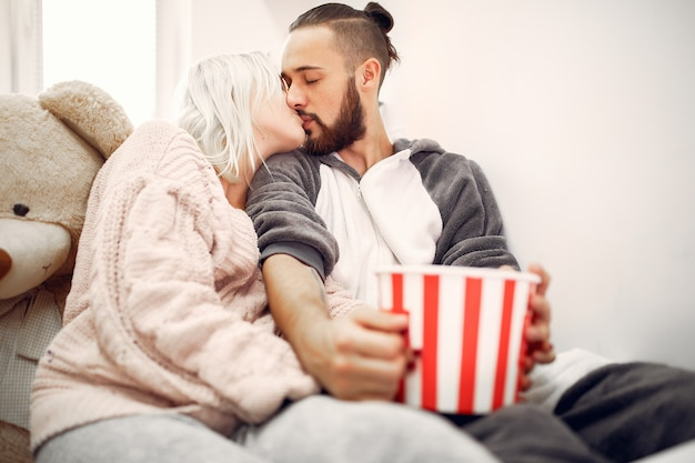 Couple kissing on a bed with a popcorn bowl