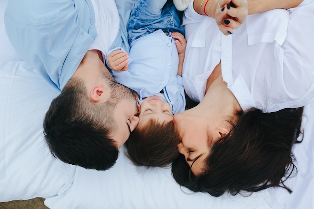 Couple kissing child on bed