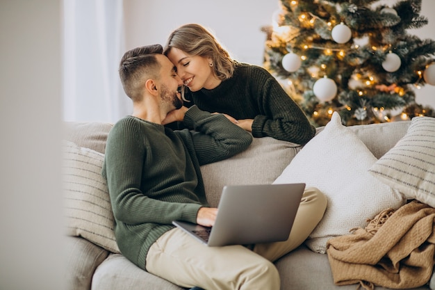 Coppia baciarsi accanto all'albero di natale, utilizzando il computer portatile