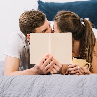 Couple kissing covering faces on bed