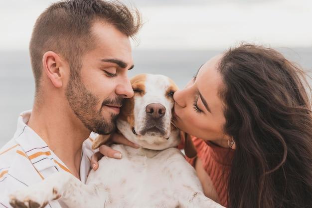 Пара целует собаку