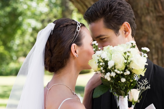 Couple kissing behind flowers in garden