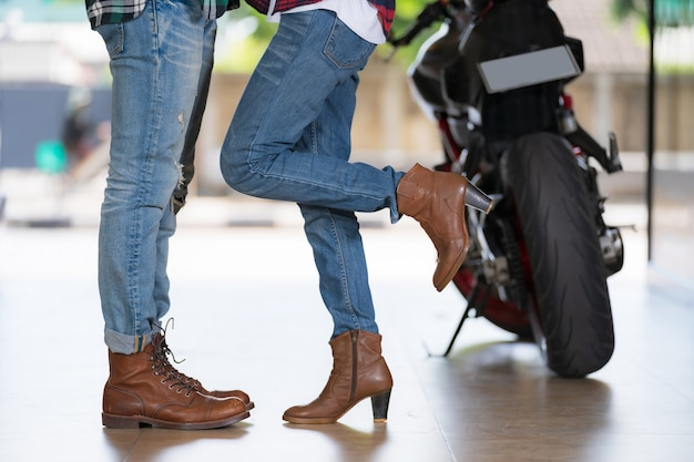 Couple kissing, girls stands on tiptoe to kiss her man with motorcycle blur background