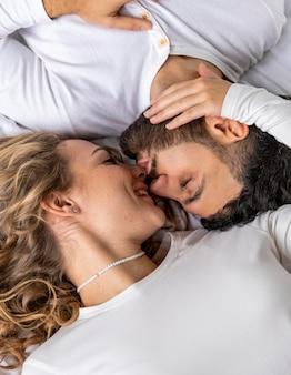 自宅のベッドでキスするカップル