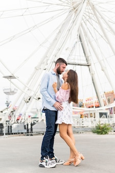 大きな車輪の前でキスするカップル