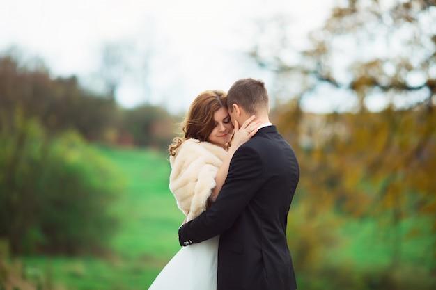 Пара целуется в медовый месяц на открытом воздухе в осеннем парке