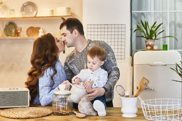 Couple kissing in the kitchen with their son