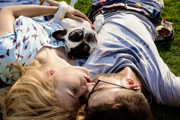 Пара целоваться, лежа с французским бульдогом на траве в парке