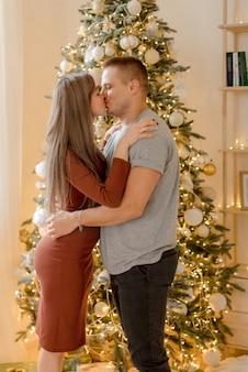 Couple kissing near a christmas tree