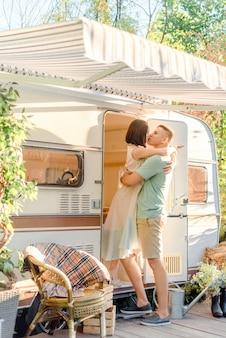 Пара целуется возле трейлера