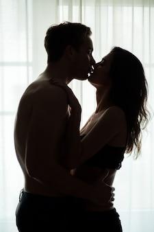 Пара, целующаяся возле окна.