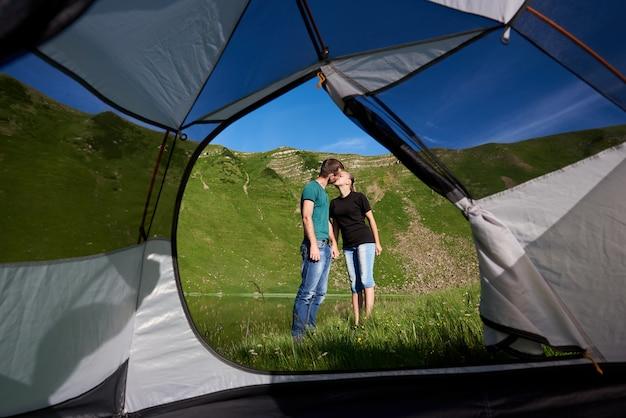 Соедините целовать на предпосылке зеленых гор и озера на ноге на солнечный день. вид изнутри палатки