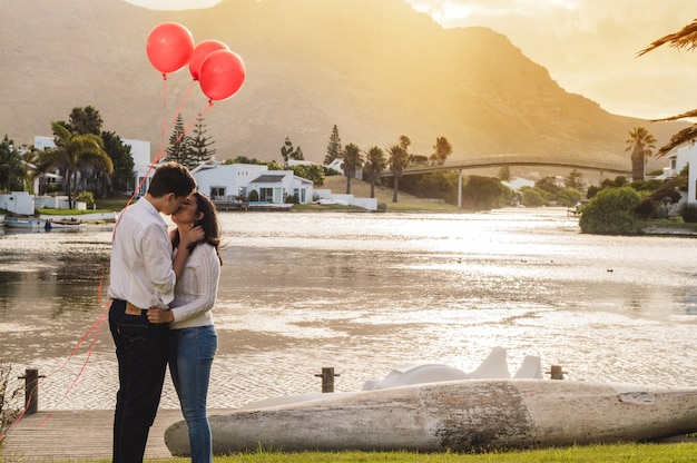 Couple kissing in a park with red balloons at sunset