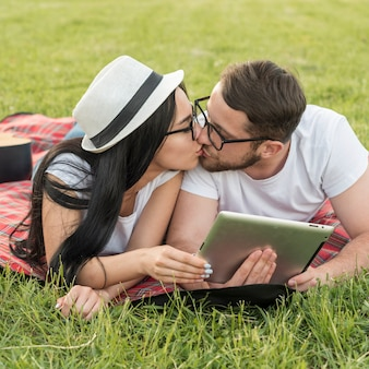 Couple kissing on a picnic blanket