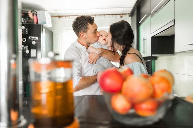 Couple kissing to their baby in the kitchen