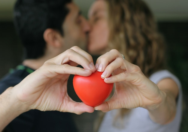 手で赤いハートを保持しながらキスするカップル