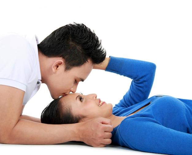 Пара целуется, лежа на полу