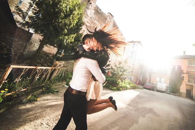 Пара поцелуев в то время как мужчина поднимает женщина