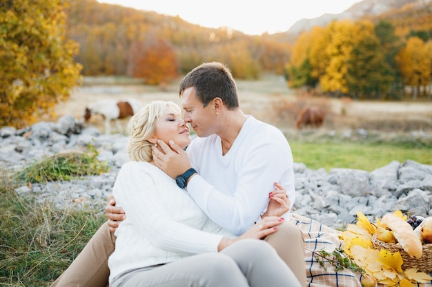 Couple kissing while sitting on a blanket against horses grazing in the autumn