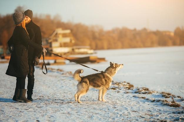 Пара целоваться во время прогулки с собакой